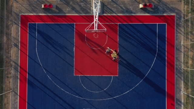 バスケットボールコート上の2人のバスケットボール選手の航空写真 - 籠点の映像素材/bロール