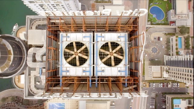 aerial view of two cooling fan spinning on the roof of the skyscraper. To the left of the building you can see the lake and to the right of the pool video