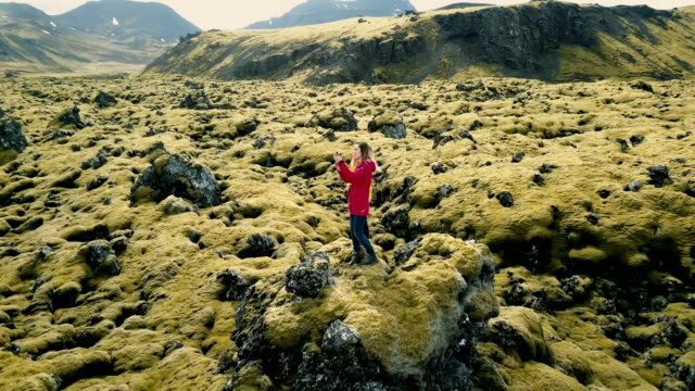 Aerial view of two happy woman standing on the lava field in Iceland and making selfie photo on smartphone