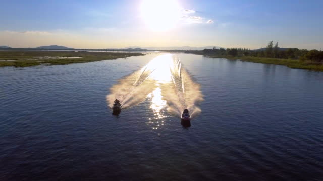 Aerial View of two Jet Boat racing in the lake at sunset video