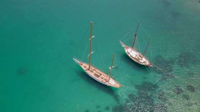 aerial view of two traditional boats in the mediterranean sea. - grecja filmów i materiałów b-roll
