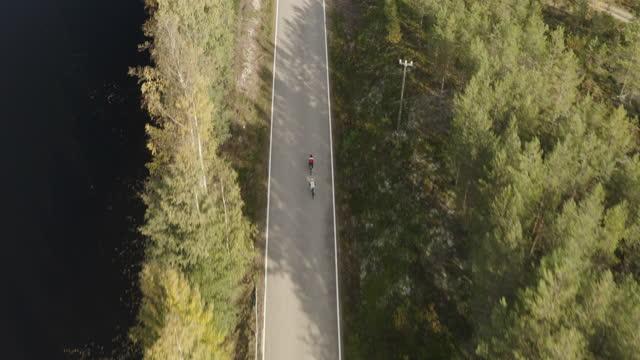 vista aerea di due triatleti in bicicletta - ciclismo su strada video stock e b–roll