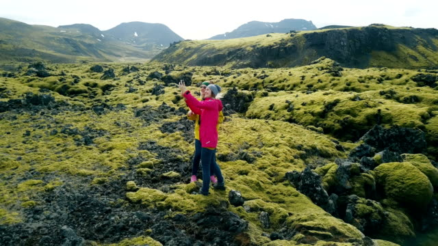Aerial view of two woman on lava field in Iceland. Copter flying around tourists taking selfie photo on smartphone