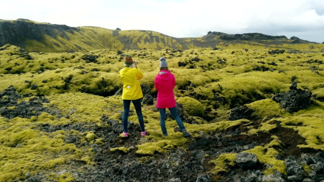 Aerial view of two woman standing on the lava field in Iceland and enjoying the landscape. Tourists after hiking