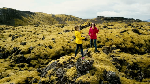 Aerial view of two woman standing on the rock, hiking together. Copter flying around tourist in lava field in Iceland