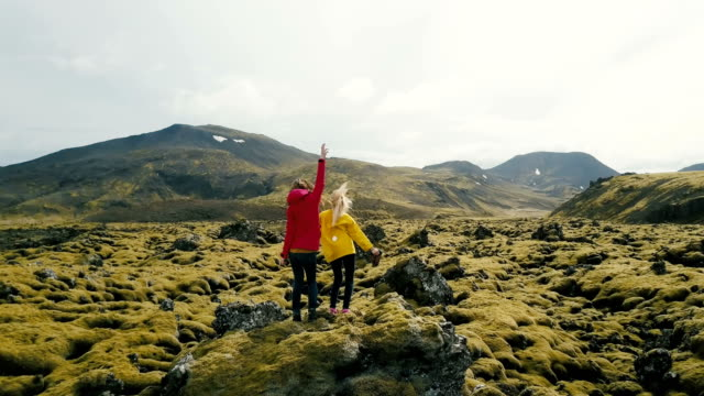 Aerial view of two woman standing on the rock in lava field in Iceland. Tourists looks on landscape, dancing and jumping video