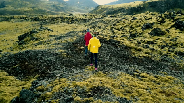 Aerial view of two woman walking on the lava field covered moss on Iceland. Tourists exploring the territory