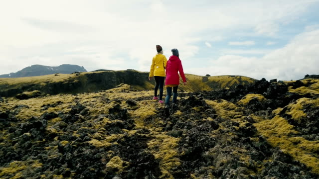 Aerial view of two woman walking on the lava field in Iceland. Tourists female hiking on the mountains covered moss video