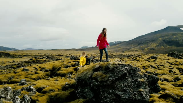 Aerial view of two woman walking on the lava field in Iceland. Tourists hiking on the rocks, feeling freedom and happy video