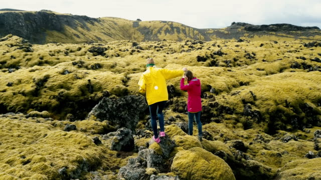 Aerial view of two woman walking on the lava field in Iceland. Tourists exploring the meadow covered moss, hiking