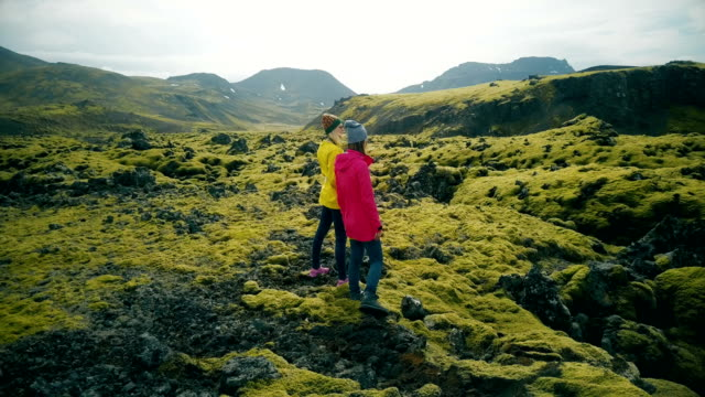 Aerial view of two woman walking on the lava fields in Iceland. Tourists enjoying the landscape, exploring the territory video