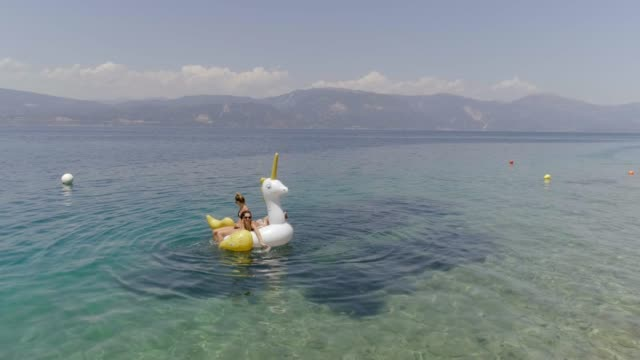 Aerial view of two women floating on inflatable in Panagopoula, Greece. Aerial view of two women floating on inflatable unicorn in Panagopoula, Greece. floating on water stock videos & royalty-free footage