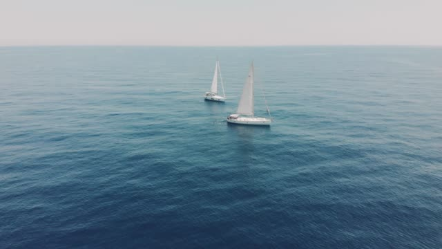 Aerial View of two yachts in the ocean, silhouettes of swimming people next to yachts. Drone footage of yachting in the Balearic islands. Unrecognizable people on yachts Aerial View of two yachts in the ocean, silhouettes of swimming people next to yachts. Drone footage of yachting in the Balearic islands. Unrecognizable people on yachts in Spain yachting stock videos & royalty-free footage