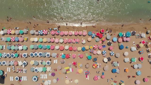 luftaufnahme von regenschirmen in einem strand der ägäis - sun chair stock-videos und b-roll-filmmaterial