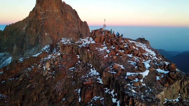 vídeos de stock e filmes b-roll de aerial view of unrecognizible climbers on summit of the lenana peak of mount kenya during sunrise - quénia