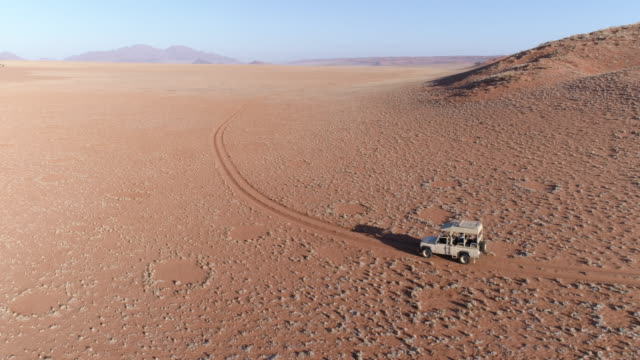 Aerial view of vehicle driving through the beautiful NamibRand Nature Reserve Aerial view of a safari vehicle driving through the vast plains of the NamibRand Nature Reserve namibia stock videos & royalty-free footage