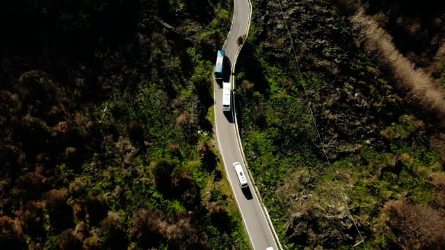 aerial view of vehicles on a narrow mountain road. tour bus stops at roadside to let oncoming cars pass. safety. 4k - passare davanti video stock e b–roll