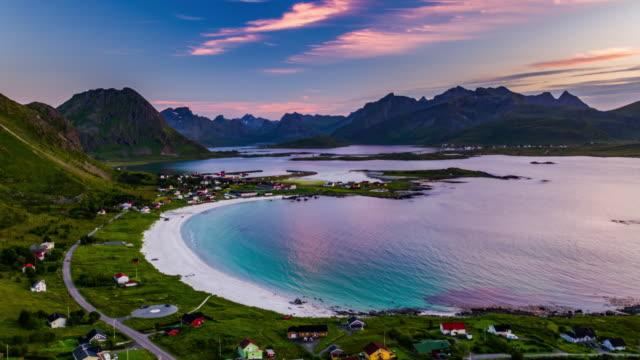 vídeos de stock e filmes b-roll de aerial view of village at the lofoten islands in norway with beautiful sandy beach at sunset - lofoten