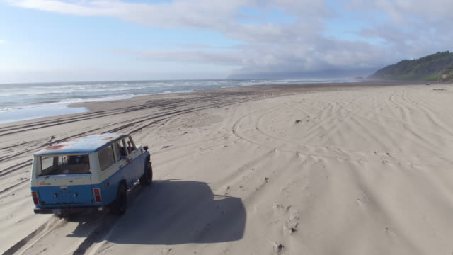 Aerial view of vintage vehicle on beach Aerial view of group of friends driving on beach in vintage vehicle beach party stock videos & royalty-free footage