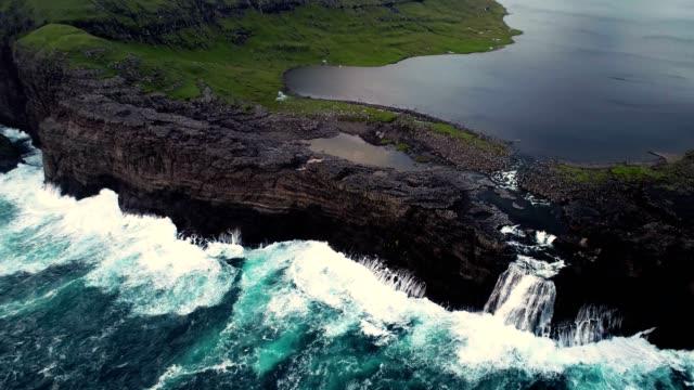 aerial view of water encountering agitated atlantic ocean, faroe island. - oceano atlantico video stock e b–roll