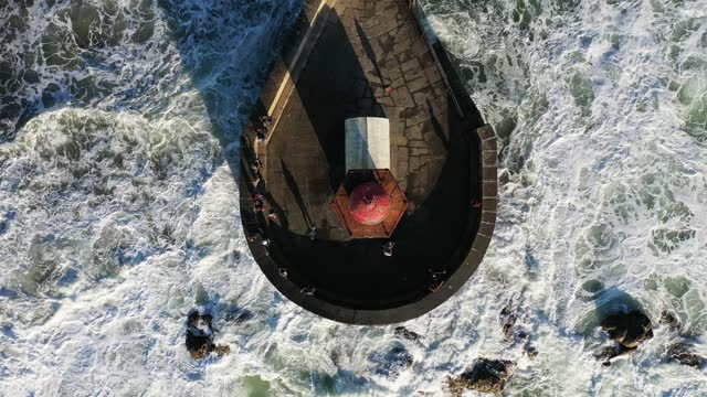 Aerial view of waves crashing around old lighthouse