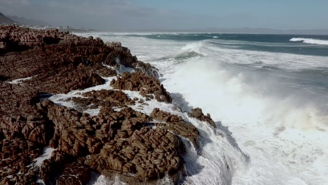 Aerial view of waves crashing into a rocky shore