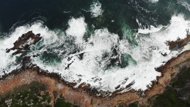 Aerial view of waves crashing on rugged African cost line high, vertical, zooming, rotating camera angle shot of waves at the cape of good hope near robberg south africa kelp stock videos & royalty-free footage