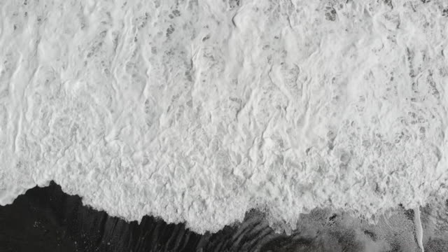 Aerial view of waves crashing onto black sand beach video
