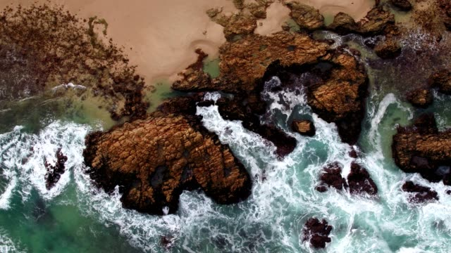 Aerial view of waves crashing onto the rocks near the beach