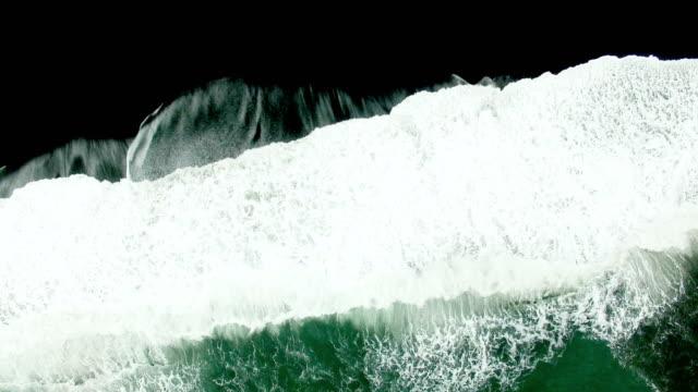 stockvideo's en b-roll-footage met luchtfoto van golven op zwarte zand strand in ijsland - rocks sea