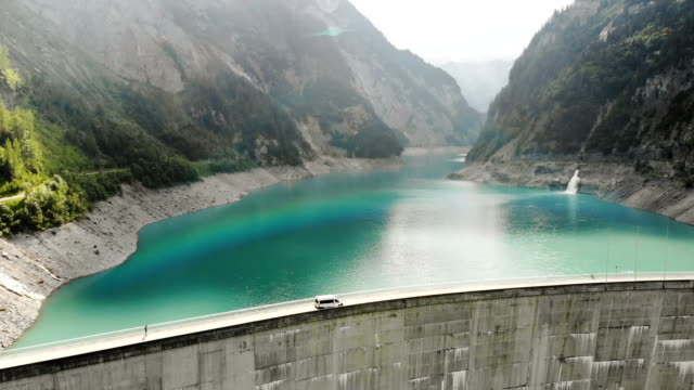 vídeos de stock e filmes b-roll de aerial view of white camper van crossing dam in swiss alps - suíça