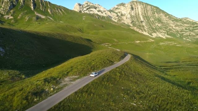 vidéos et rushes de vue aérienne de voiture blanche conduisant sur la route serpentine de montagne dans les lumières de coucher du soleil. tir de drone 4k aérien - voiture blanche