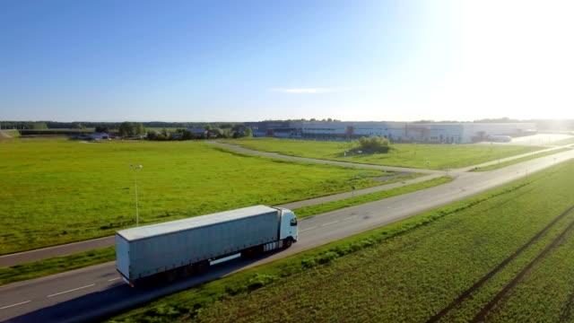 高速道路移動貨物トレーラーと白半トラックの空撮。背景倉庫、農村地域では、太陽が輝いています。 - トラック点の映像素材/bロール