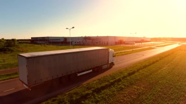 flygfoto över vit semi truck med last släpfordonet rör sig på motorvägen. i bakgrunden lagerställen och industriella lastning byggnader ses. solnedgång. - shipping sunset bildbanksvideor och videomaterial från bakom kulisserna