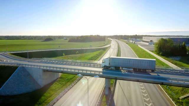 aerial view of white semi truck with cargo trailer passing highway overpass/ bridge. eighteen wheeler is new, loading warehouses are seen in the background. - тягач с полуприцепом стоковые видео и кадры b-roll