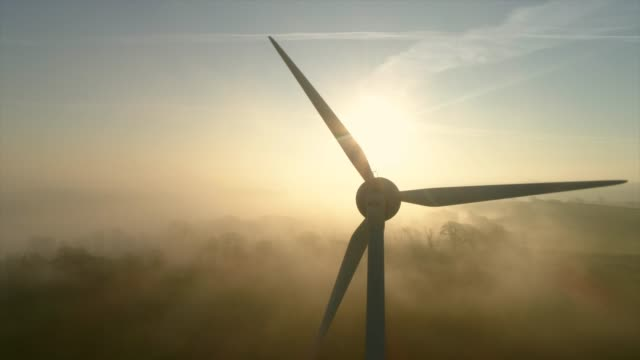 aerial view of wind turbine at sunset - turbina a vento video stock e b–roll