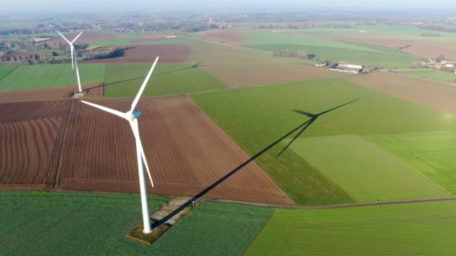Aerial view of wind turbines and agricultural fields on a blue winter day video