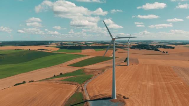 flygfoto över vindkraftverk och vinden gernerators i rörelse på en sommardag över vete grödor med med stor öppen himmel - vindsnurra jordbruksbyggnad bildbanksvideor och videomaterial från bakom kulisserna