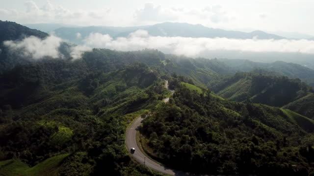 vista aerea della strada tortuosa sulla montagna e sulla guida in auto, concetto di guida di sicurezza - strada tortuosa video stock e b–roll