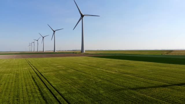 aerial view of windmills station with rotating propellers generating alternative clean green power from eco resources in rural agri environment - clima video stock e b–roll