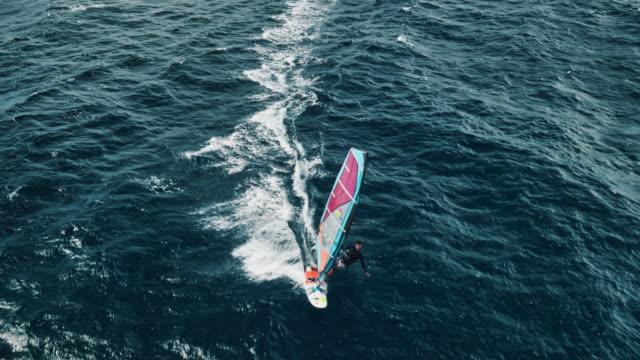 Aerial view of windsurfer gliding across blue ocean video
