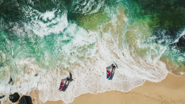 Aerial view of windsurfers launching from white sand beach into blue ocean video