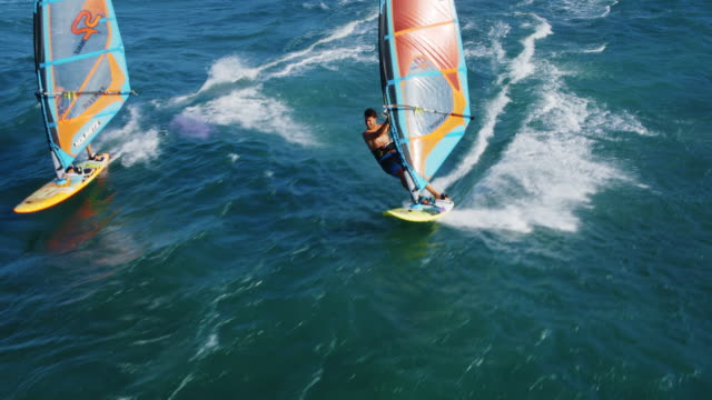 Aerial View of Windsurfing Cinematic aerial view of windsurfers sailing across the ocean hawaii islands stock videos & royalty-free footage