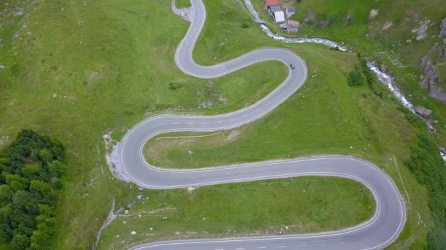 aerial view of windy hairpin turns on steep mountain road - livigno video stock e b–roll