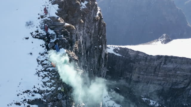 aerial view of wingsuit pilot jumping off alpine cliff - base jumping video stock e b–roll