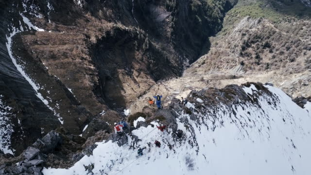 Aerial view of wingsuit pilots jumping off alpine cliff video