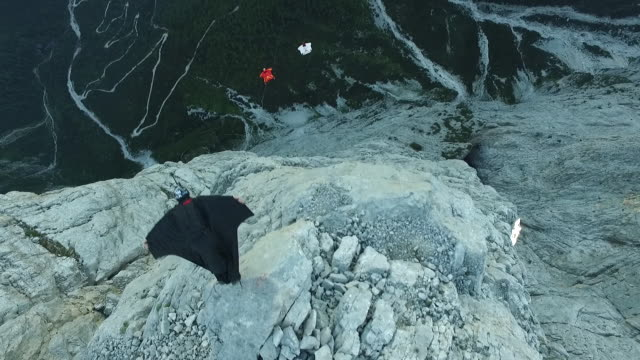 aerial view of wingsuit pilots jumping off cliff - base jumping video stock e b–roll