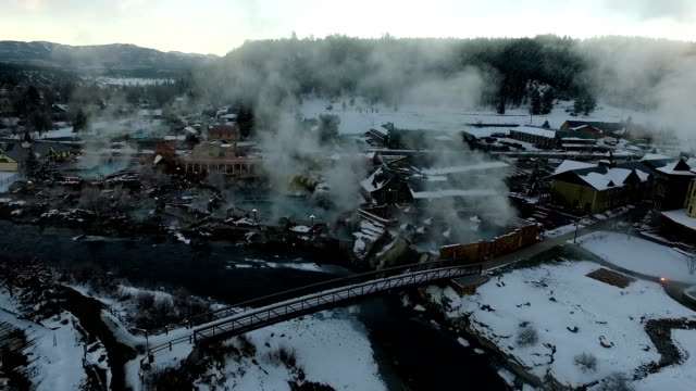 Aerial View of Winter Wonderland Pagosa Springs Colorado Bridge over San Juan River Hot Springs Steam Lifting Winter Snow Covered Rocky Mountains video