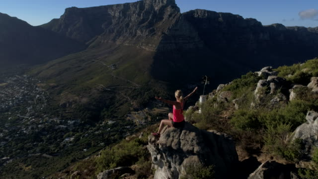 Aerial view of woman celebrating achievement on mountain top Aerial view of a young woman reaching the top of Lion's head mountain in Cape Town, South Africa. table mountain national park stock videos & royalty-free footage