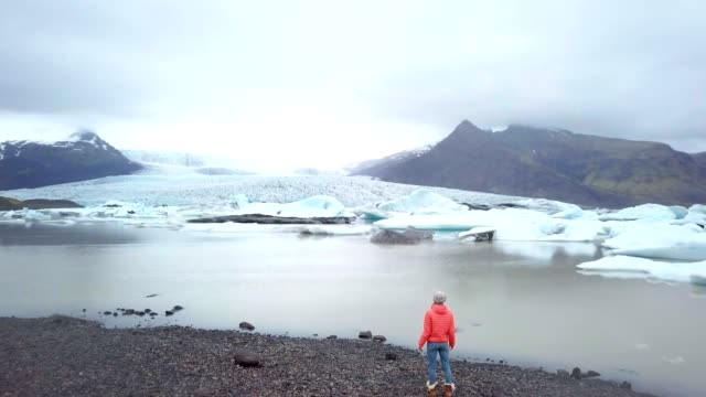 drone aerial view of woman contemplating glacier lagoon in iceland standing on lake shore - lakeshore stock videos & royalty-free footage